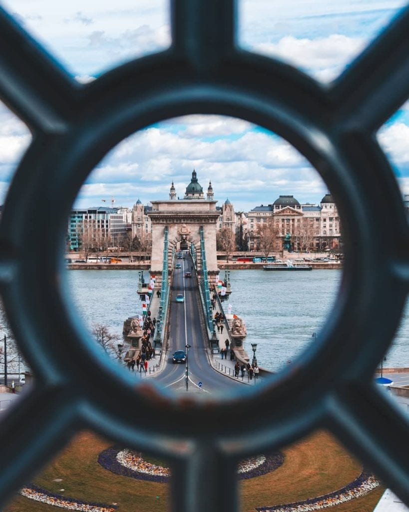 Budapest Chain Bridge seen through metal hole looking toward Buda across the Danube.