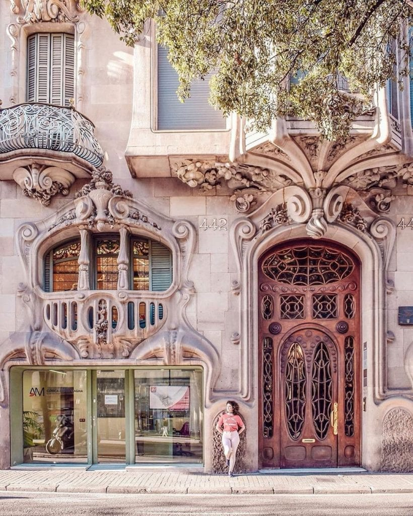 Woman leaning outside the door of Casa Comalat, one of the most beautiful places in Barcelona.