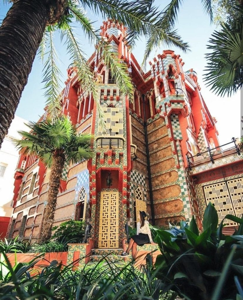 Exterior of Casa Vicens as seen from behind palm trees and other plants, one of the most beautiful places in Barcelona.