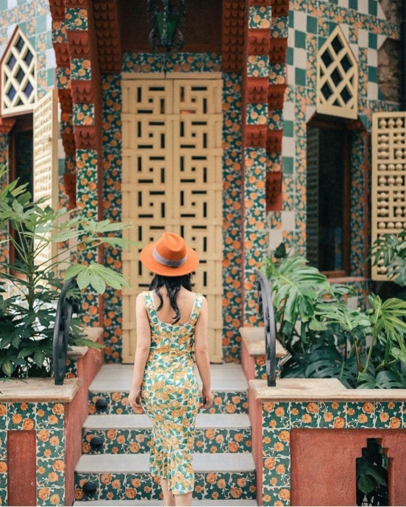Woman in floral dress standing facing Casa Vicens, her floral dress matching the floral exterior of the building.