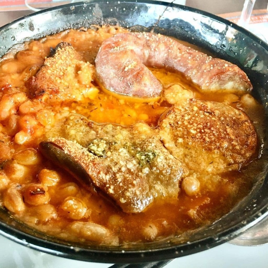 Large dish of cassoulet with white beans and sausages, a traditional French food.