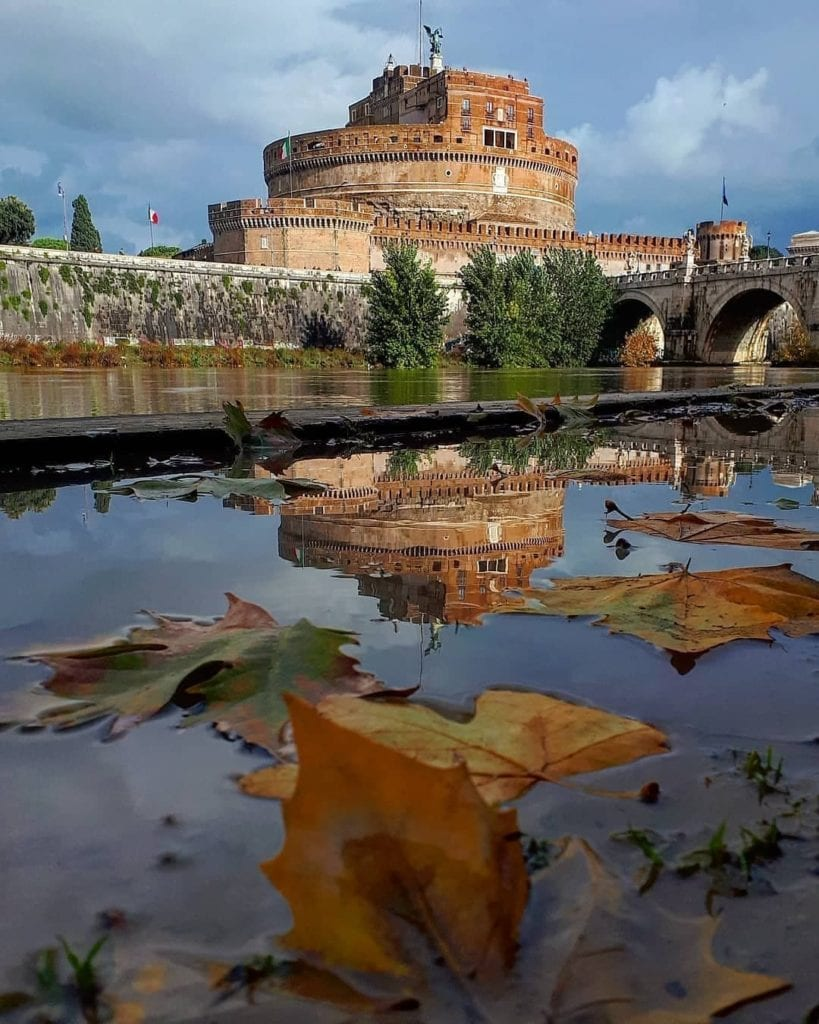 Castel Sant'Angelo, one of the most Instagrammable places in Rome, seen during autumn looking up from the Tiber with fallen leaves on the river.