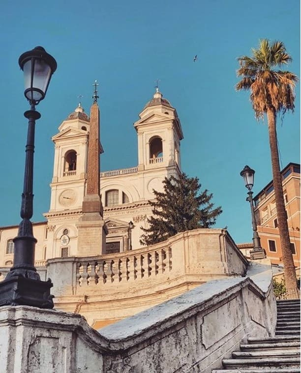 Looking up the Spanish Steps in Rome toward the Chiesa della Trinita dei Monti with some palm trees and a lamp post in the foreground.