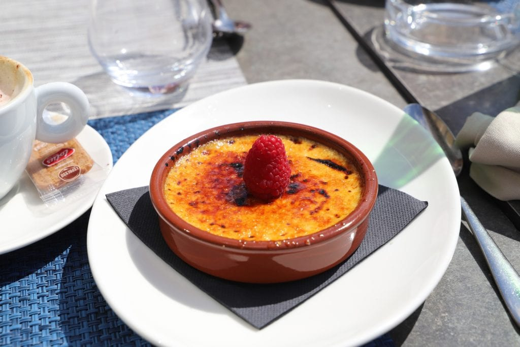 Creme brulee on a white dish with water glasses in the background, topped with a single raspberry.