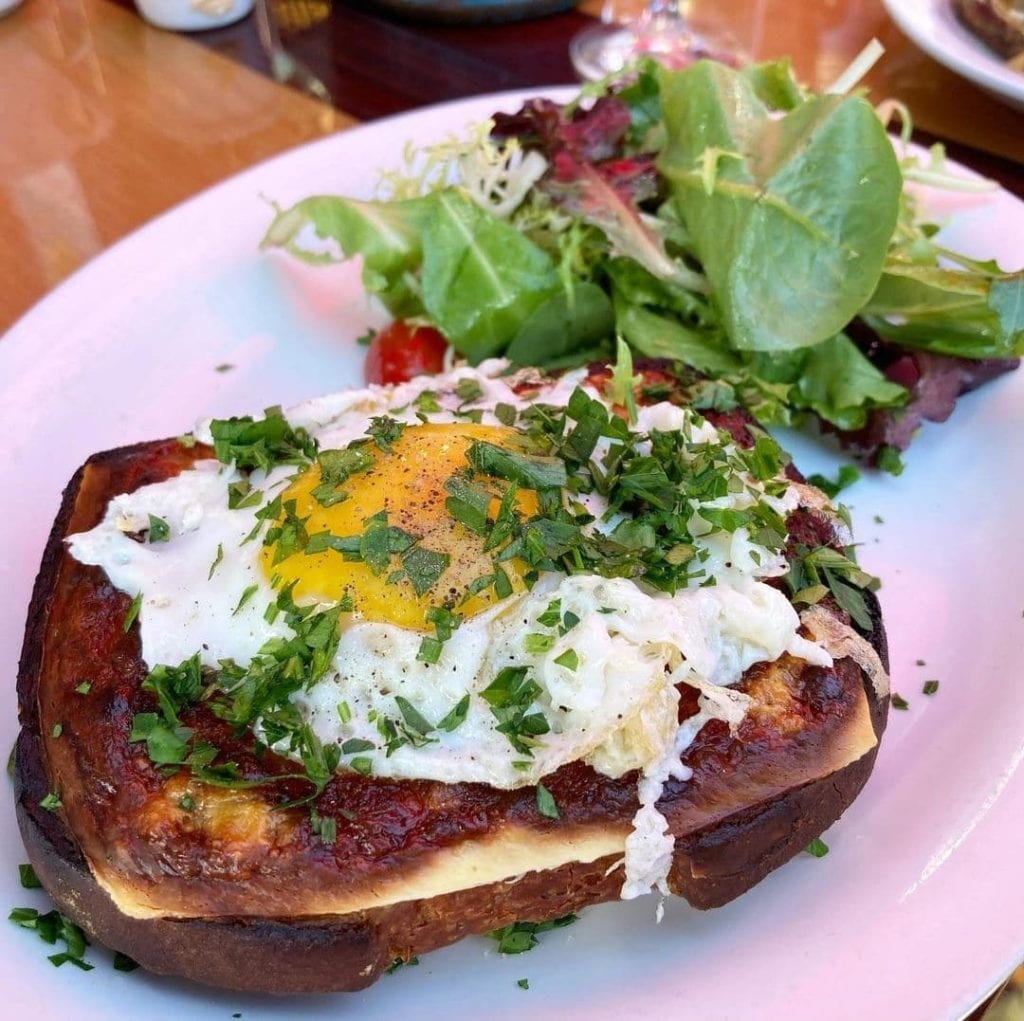 Grilled sandwich with a fried egg on top, aside a salad - croque madame, an iconic French food.