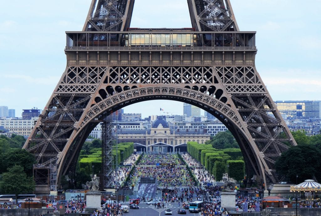 Crowds under the base of the Eiffel Tower in Paris, France.