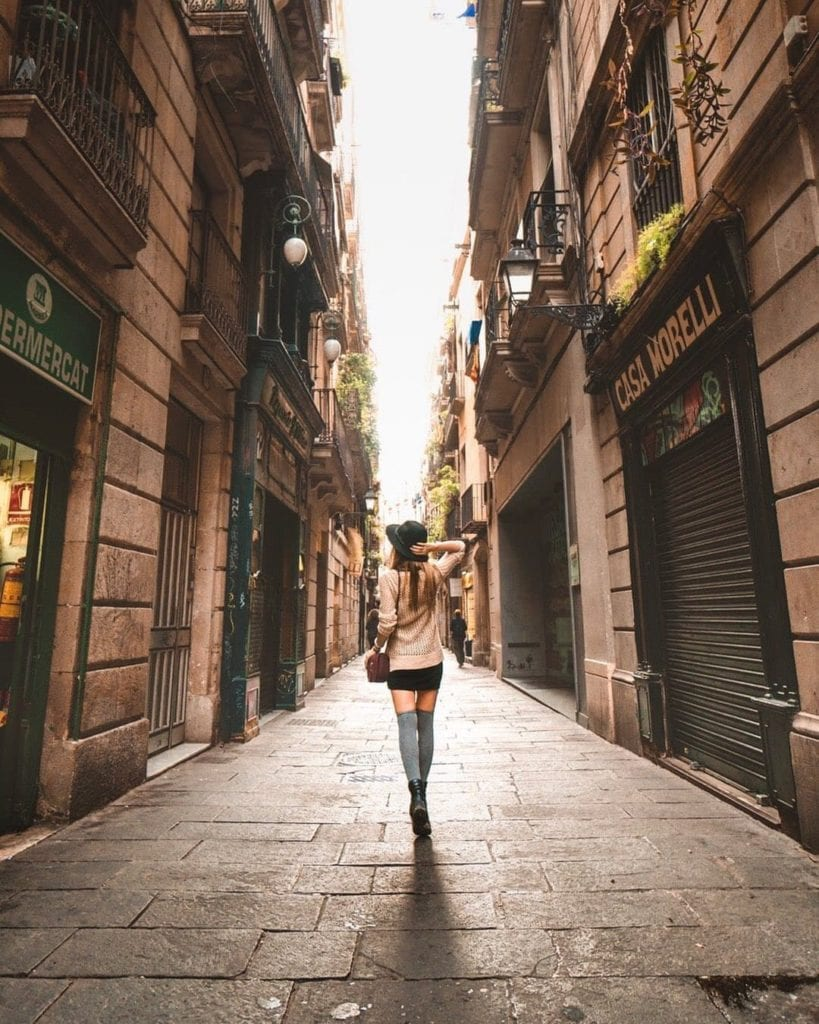 Woman in short skirt and hat walking down a narrow street in Barri del Born, one of the most beautiful places in Barcelona.
