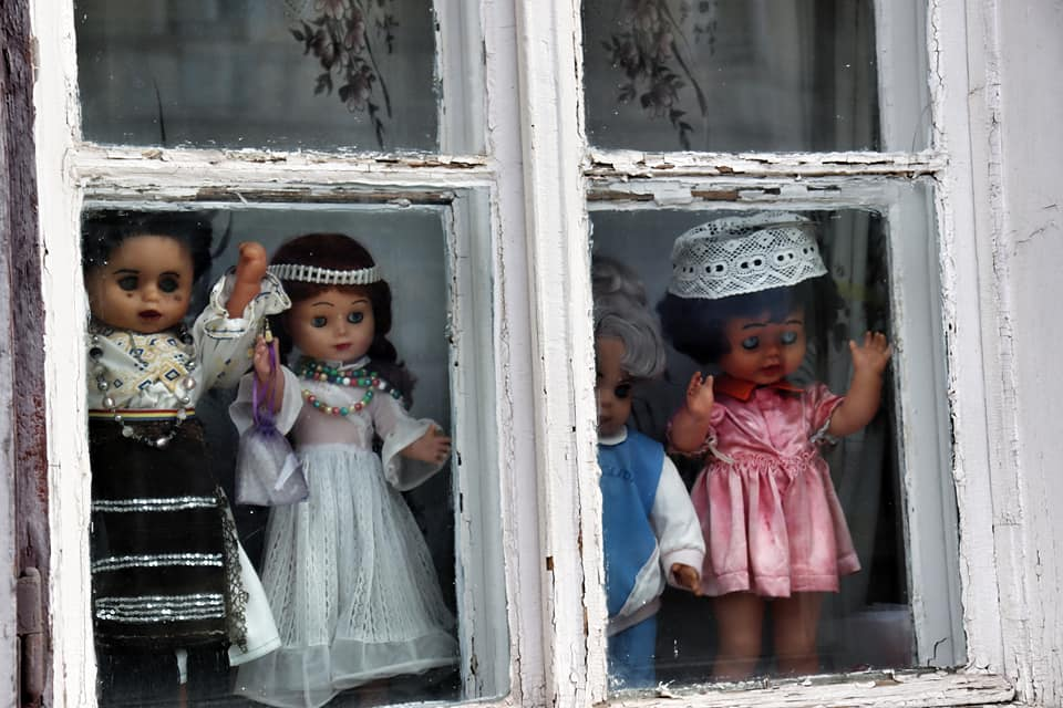 Dolls looking out a window in Sibiu, Romania