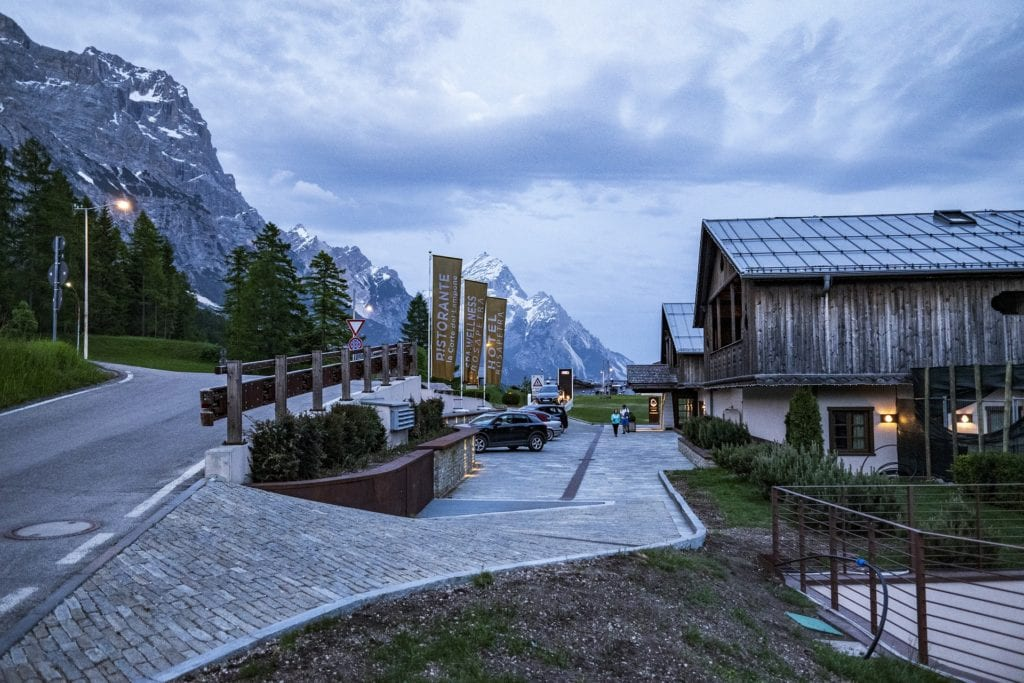 Cortina, Italy with dolomites in the background and a restaurant to the right.