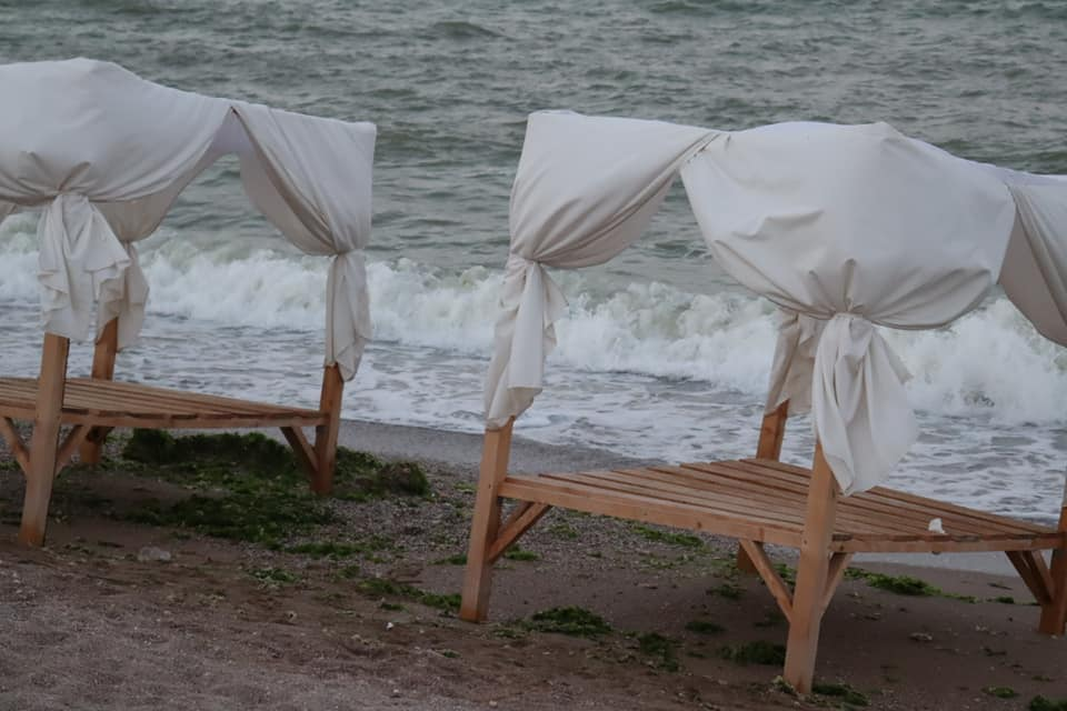 Empty canopied beach beds with white curtains on the shore.