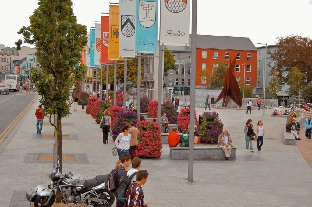 People walking around in Eyre Square, Galway City, Ireland with tribe banners hanging on lamp posts.
