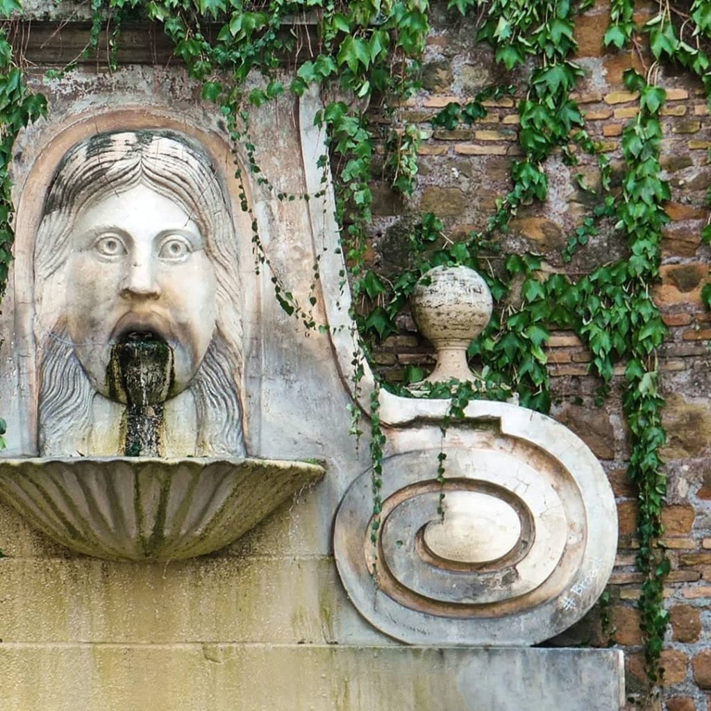Close-up of fountain in Rome with a man's face surrounded by ivy climbing a stone wall.