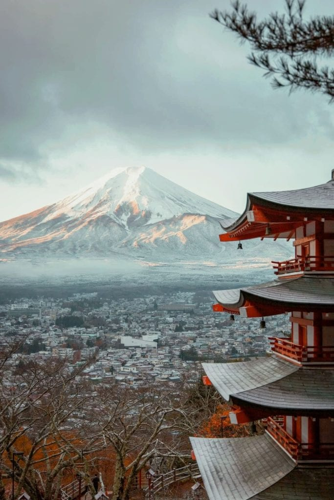 Mt Fuji covered in snow with red, snow-capped Japanese temple in foreground, one of the most popular virtual tours of Asia.