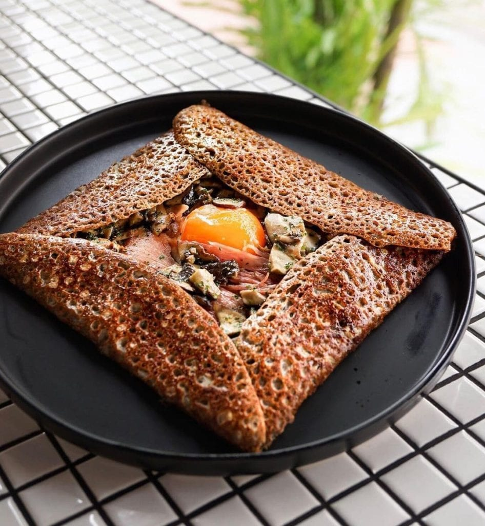 Brittany-style crepe folded into a square with a poached egg visible inside.
