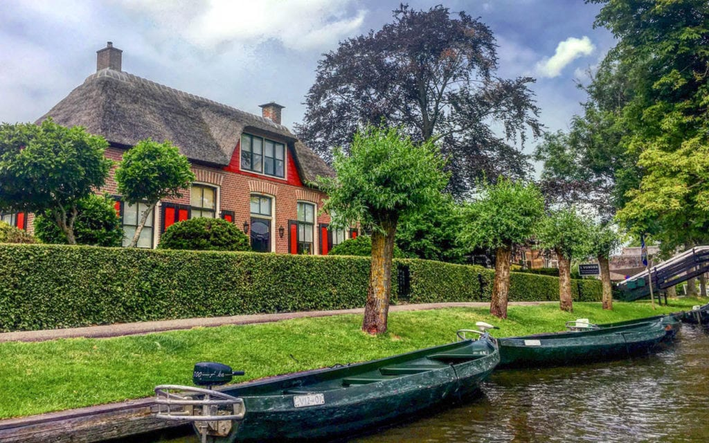 View of one of the canals in Geithoorn, Netherlands.  There are trees lining the canals and small, long boats.  Geithoorn is one of the best cities to visit in the Netherlands.