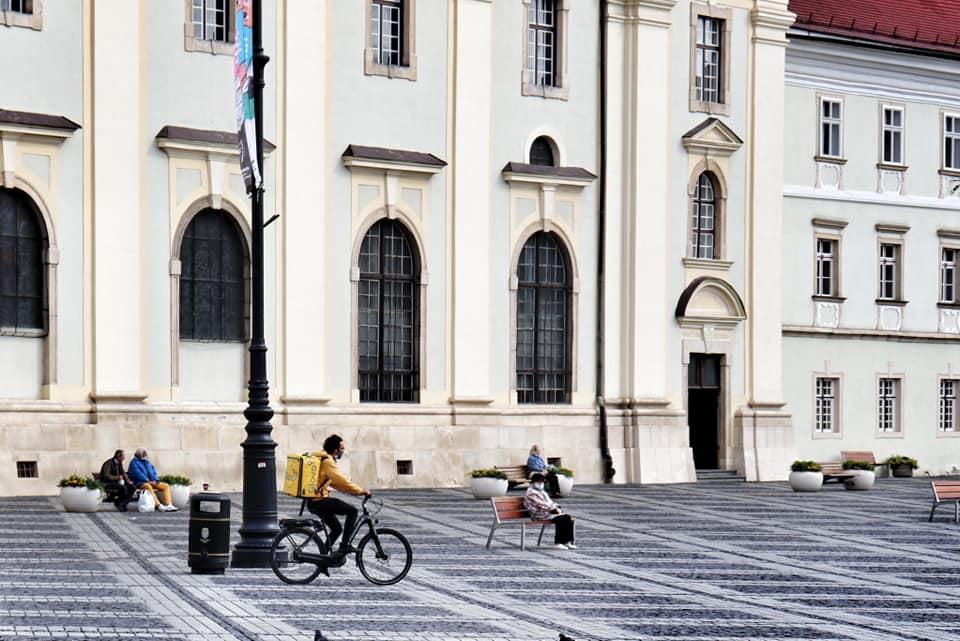 delivery man on a bicycle in PIata Mare, Sibiu, Romania