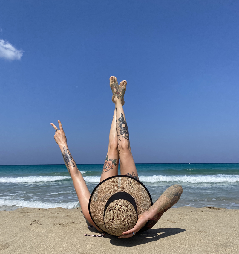 Tattooed woman lying on the shores of Kos Island, Greece, in a unique pose concealing her face.