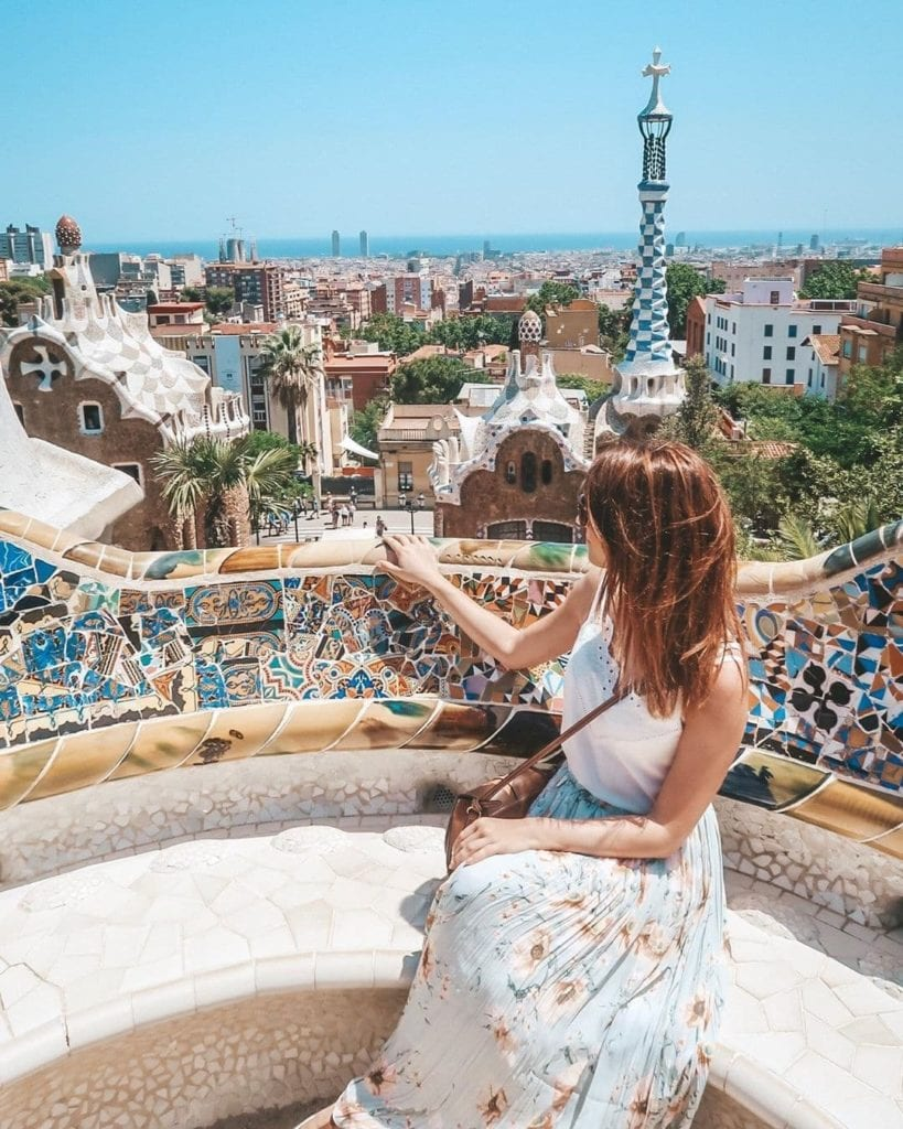 Woman sitting on a colorful tiled bench at Parc Guell, one of the most beautiful places in Barcelona.