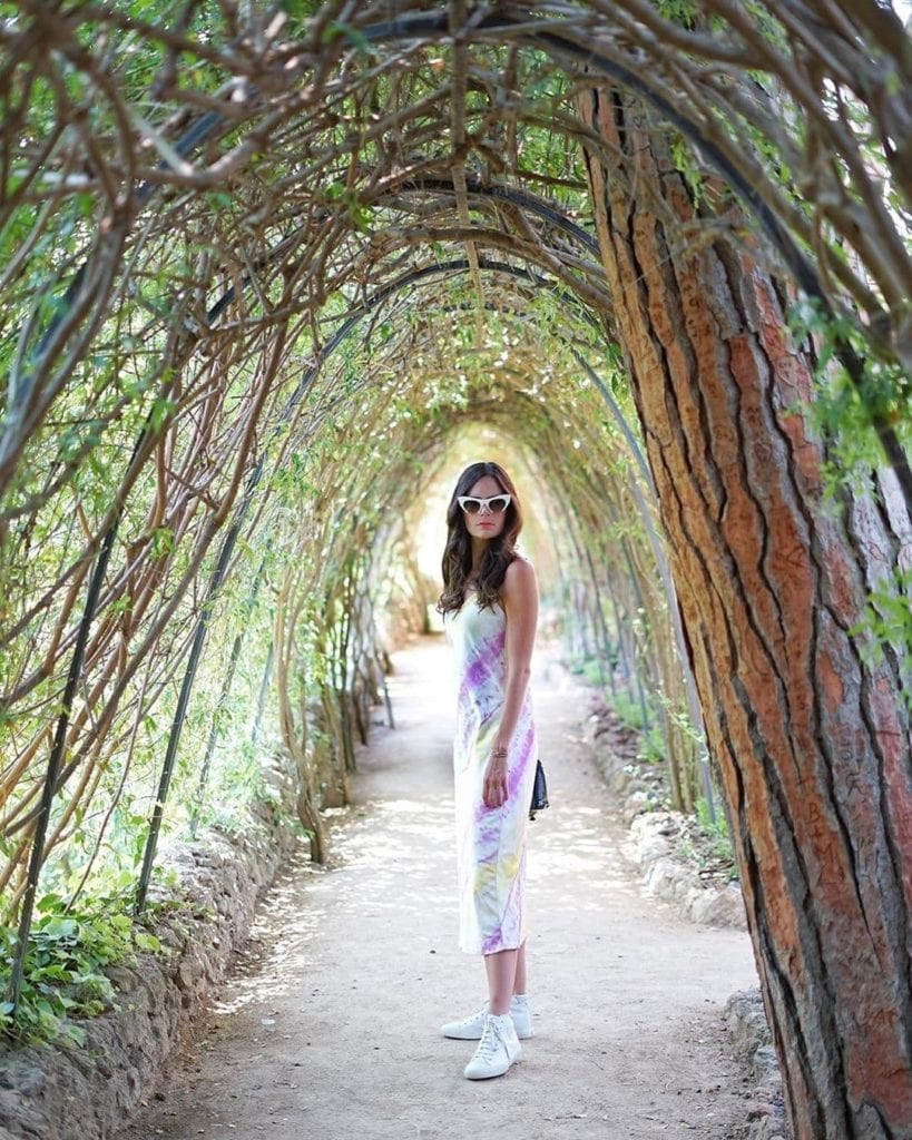 Woman in retro sunglasses posing under an arc made of trees at Parc Guell, one of the most beautiful places in Barcelona.