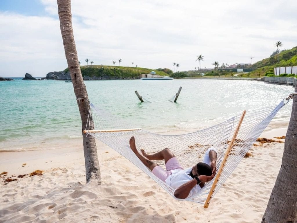 Man relaxing on a hammock at the Princess Hamilton on one of the pink sand beaches in beautiful Bermuda
