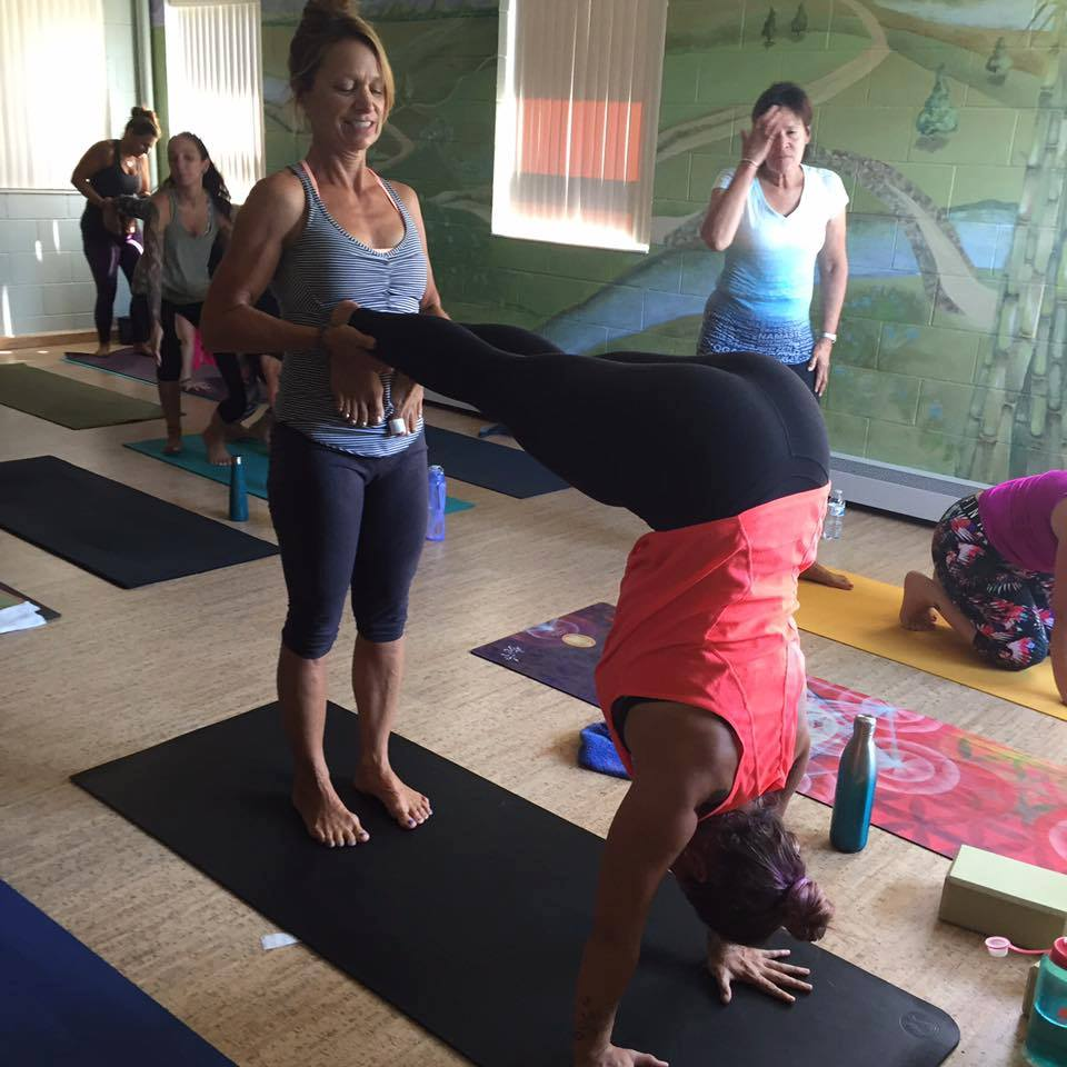 Group of yoga teacher trainees practicing handstand assists during training.