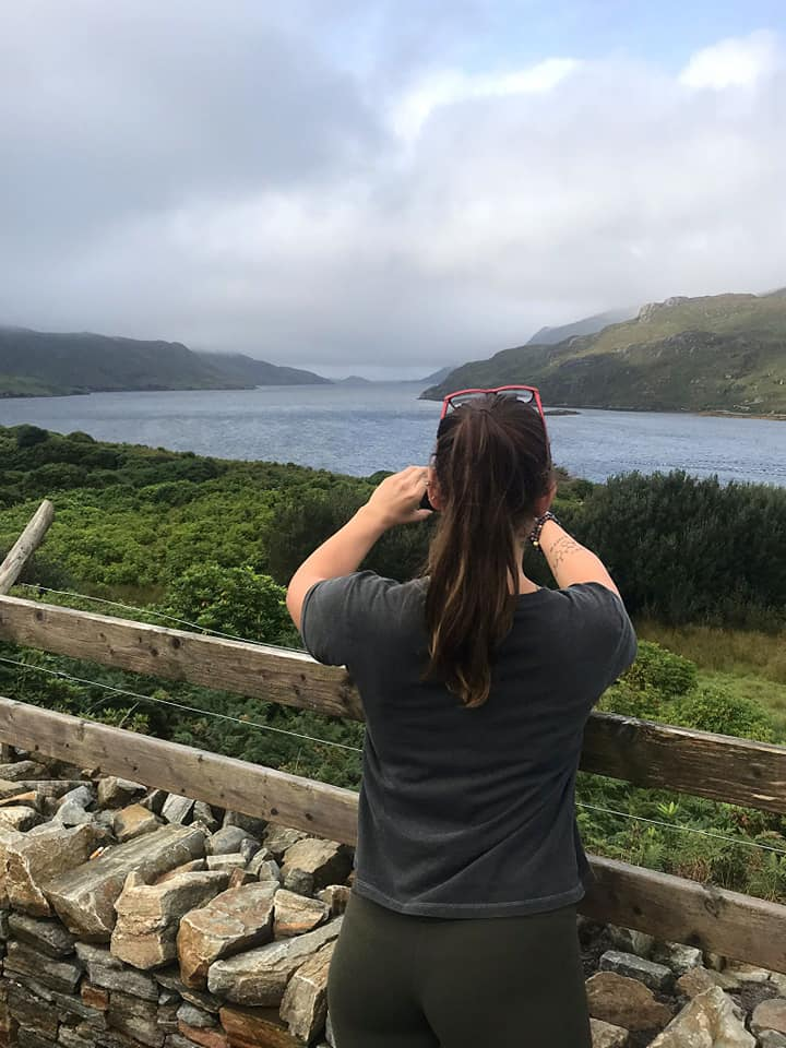 Woman from behind taking photo of Killary Fjord.