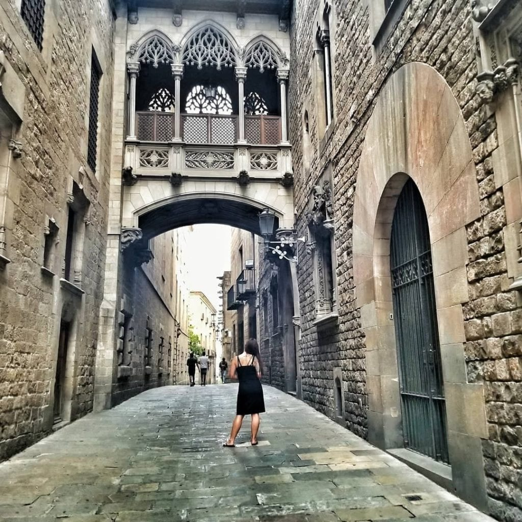 Woman standing in black dress, shot from behind, under Pont del Bisbe, one of the most beautiful places in Barcelona.