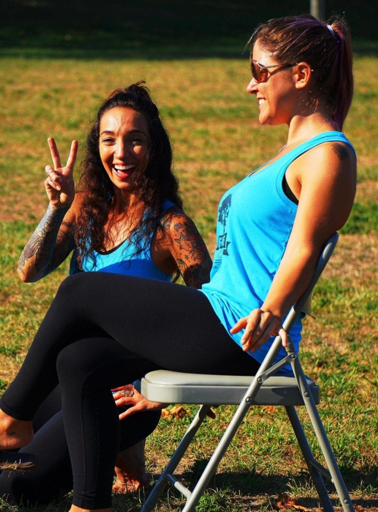 Two women on a lawn getting ready to teach a yoga class, smiling with matching turquoise tank tops.