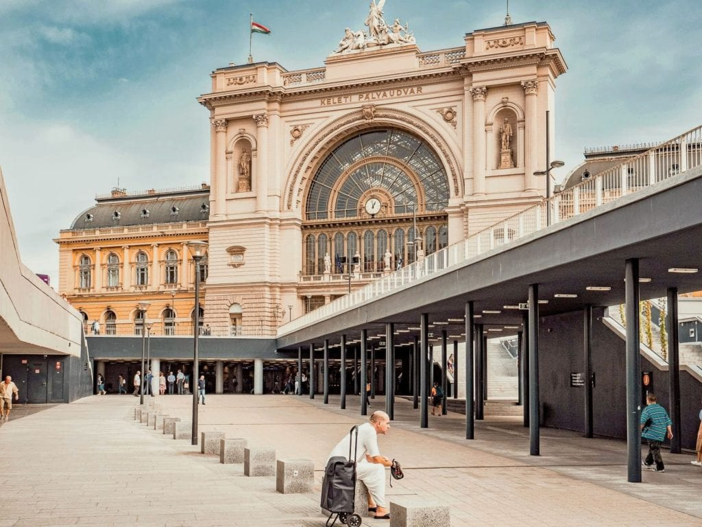 Main entrance of Budapest Keleti Train Station with a man sitting on a suitcase outside.