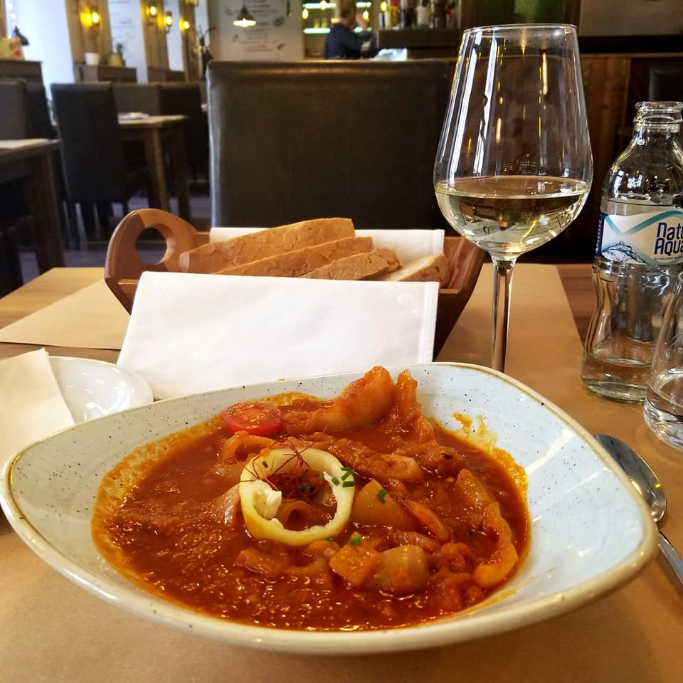 Vegetarian Hungarian stew on a set table alongside a glass of white wine and a basket of bread.