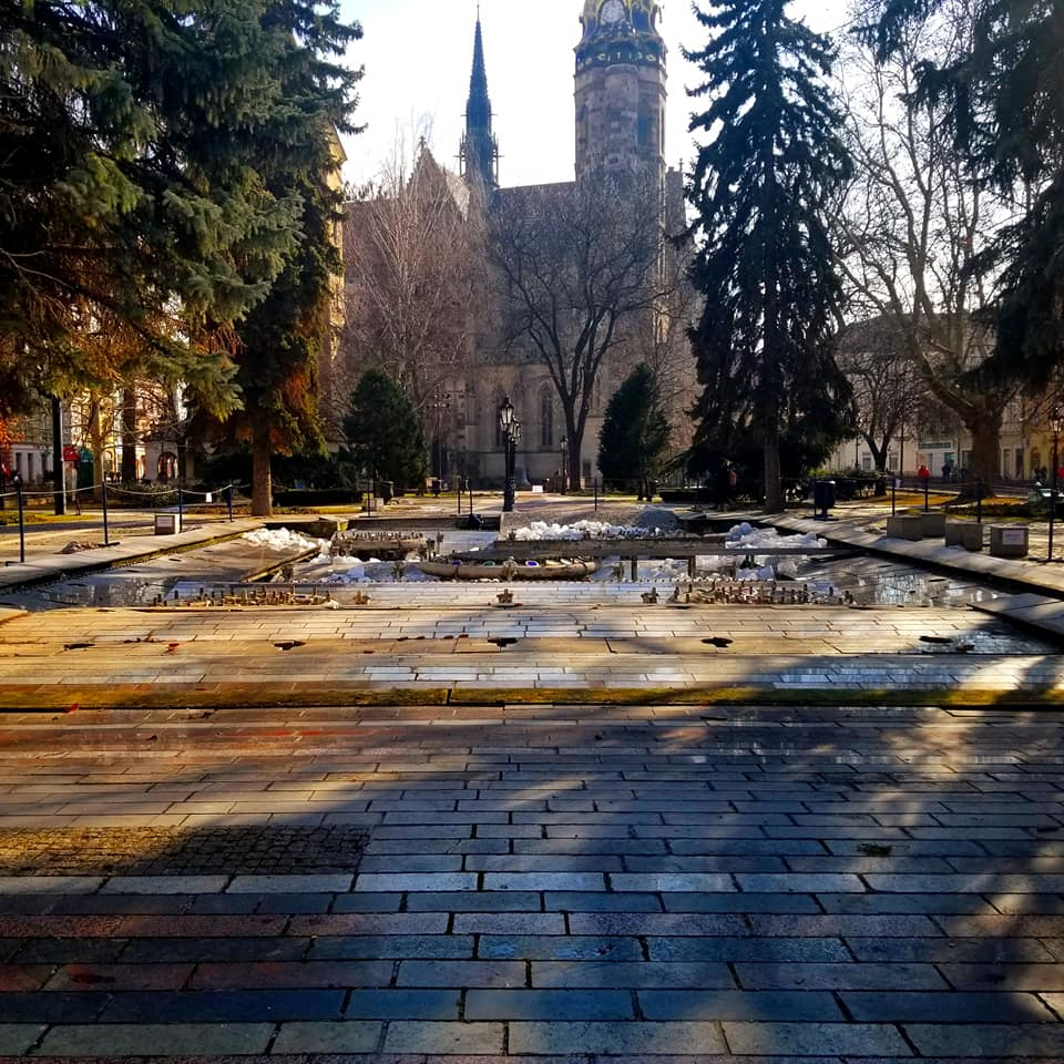 The Singing Fountain in Kosice, Slovakia - not operating.  It is winter and the fountain is covered with snow, puddles, and leaves.  Light is flooding in through the trees.  St. Elisabeth Cathedral is in the background.