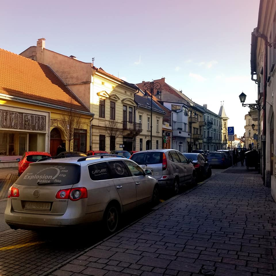 Street in Kosice, Slovakia lined with cars with the sun going down and reflecting light on the buildings.  There is a purple hue to the sky and yellow-golden shadows on the rooftops of the buildings.  Both the street and the sidewalks are made of cobblestone.  It is winter and on the few trees lining the street, there are no leaves.