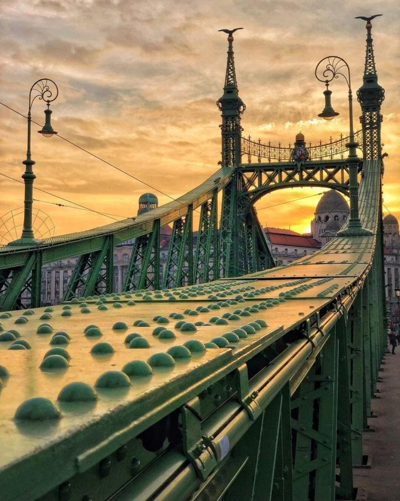 Liberty Bridge in beautiful Budapest during sunset with a yellow-orange sky.
