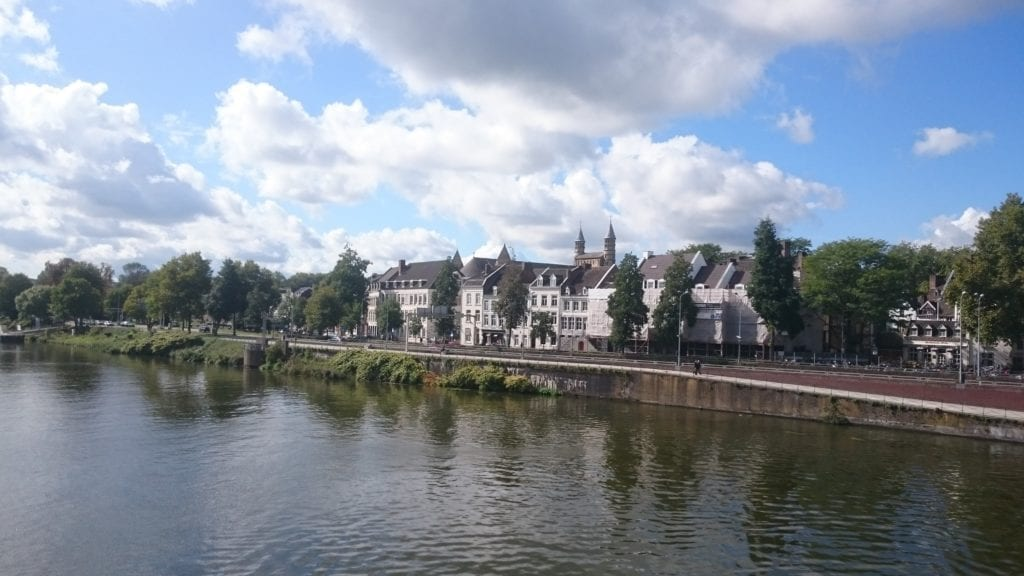 View of buildings across the canal in Maastricht, Netherlands, one of the best cities to visit in the Netherlands.  There are many trees and a few clouds in the sky reflecting in the water.