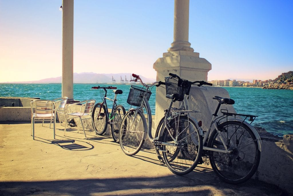 Bicycles leaning on a seaside building in Malaga, Spain.