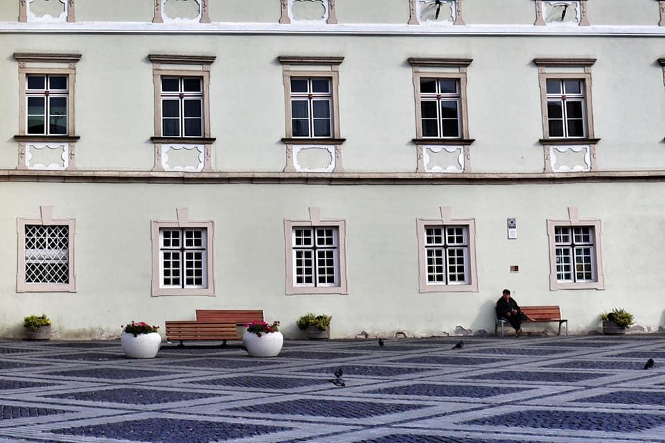 Man sitting alone on a park bench in empty Piata Mare - Sibiu, Romania