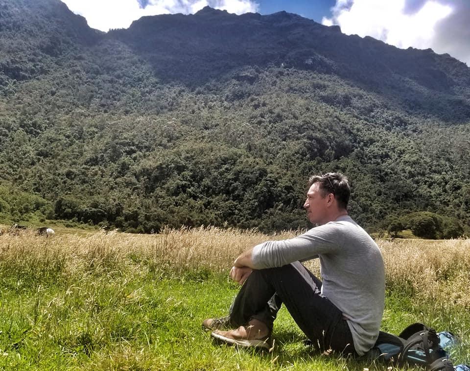 Man sitting in front of mountains in Cuenca, Ecuador - El Cajas