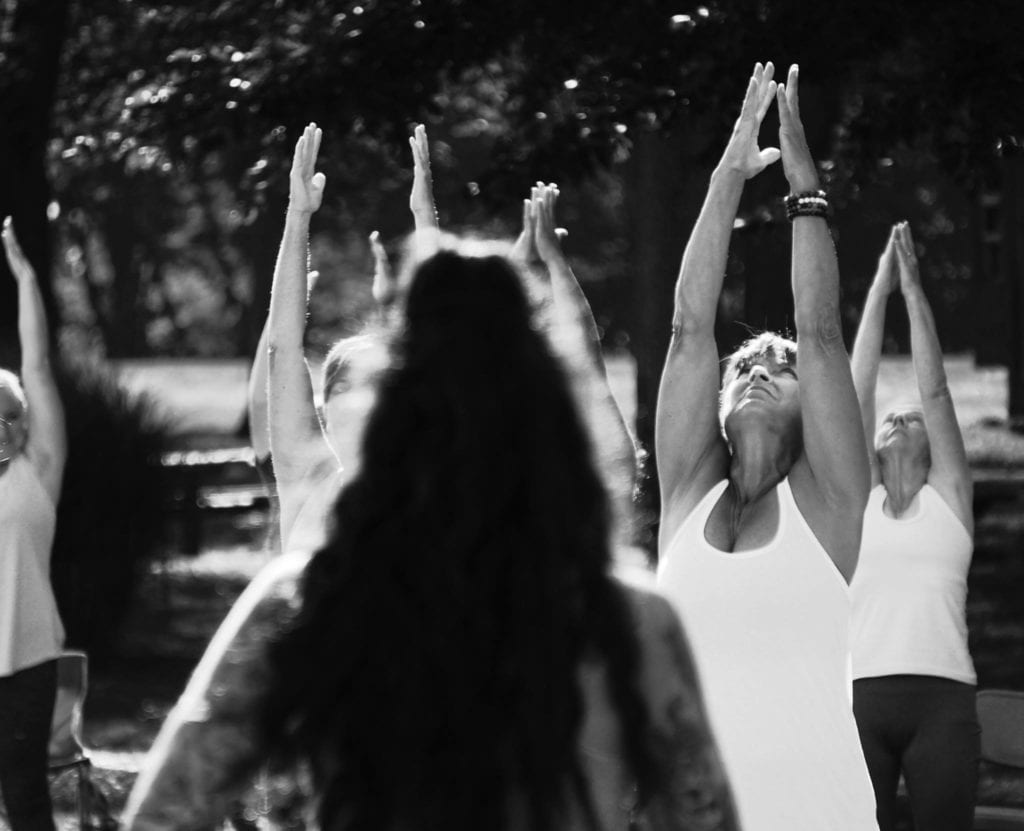 Black and white photo of group doing yoga in park.