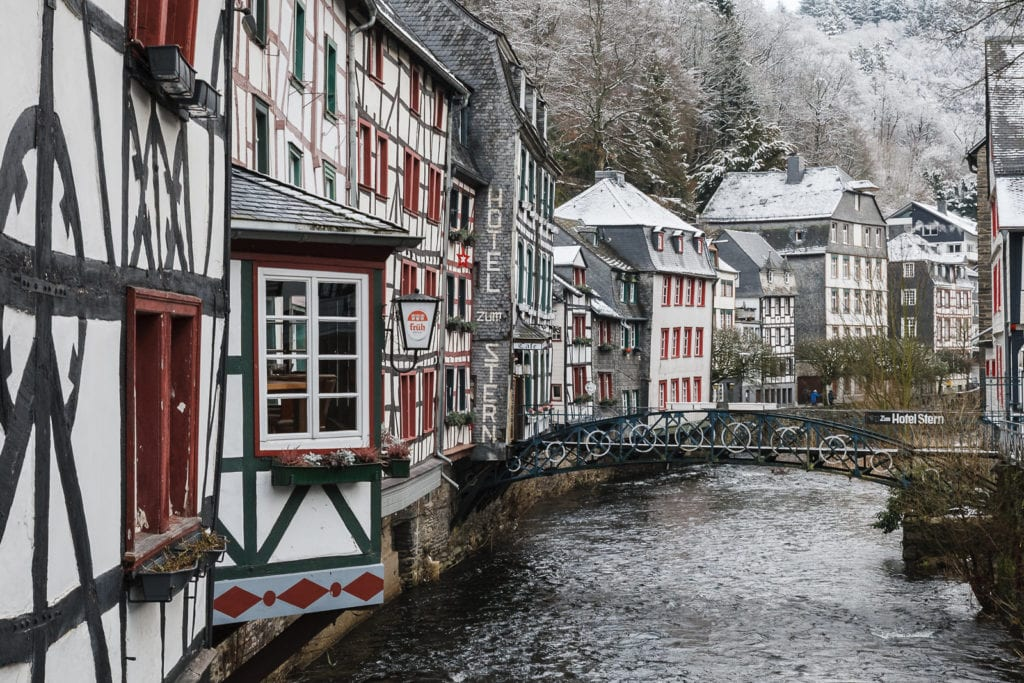 Snow covered Monschau, one of the most magical places to visit in Germany, a riverfront town.