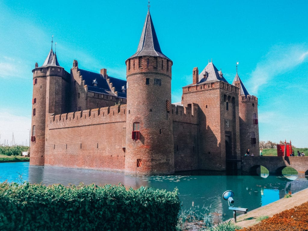Image of Muiden Castle in the Netherlands.  The castle is surrounded by blue water and the skies are bright without clouds.