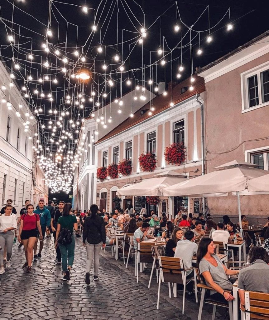 Strung lights hanging above a cobblestone street in Cluj-Napoca, Romania.