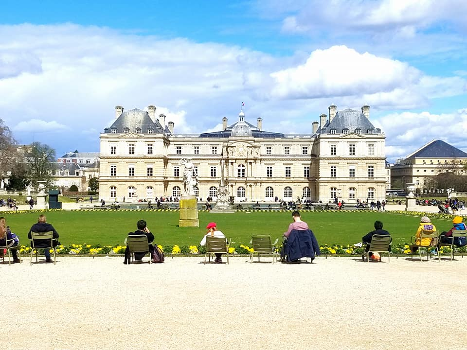 Parisians sitting around the grass at the Jardins du Luxembourg under blue skies with puffy white clouds.