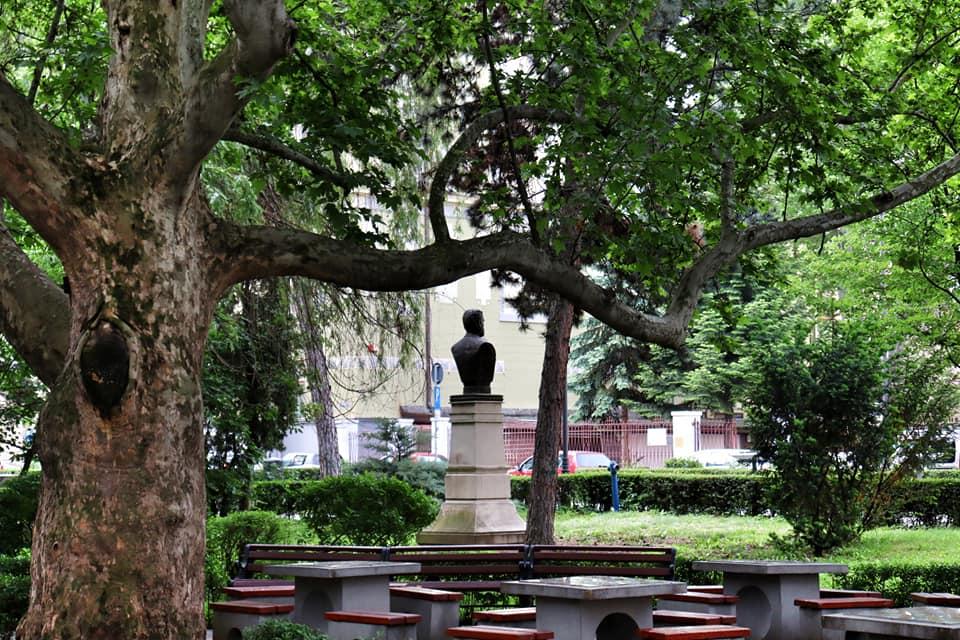 Empty tables and statue head in a park in Sibiu, Romania