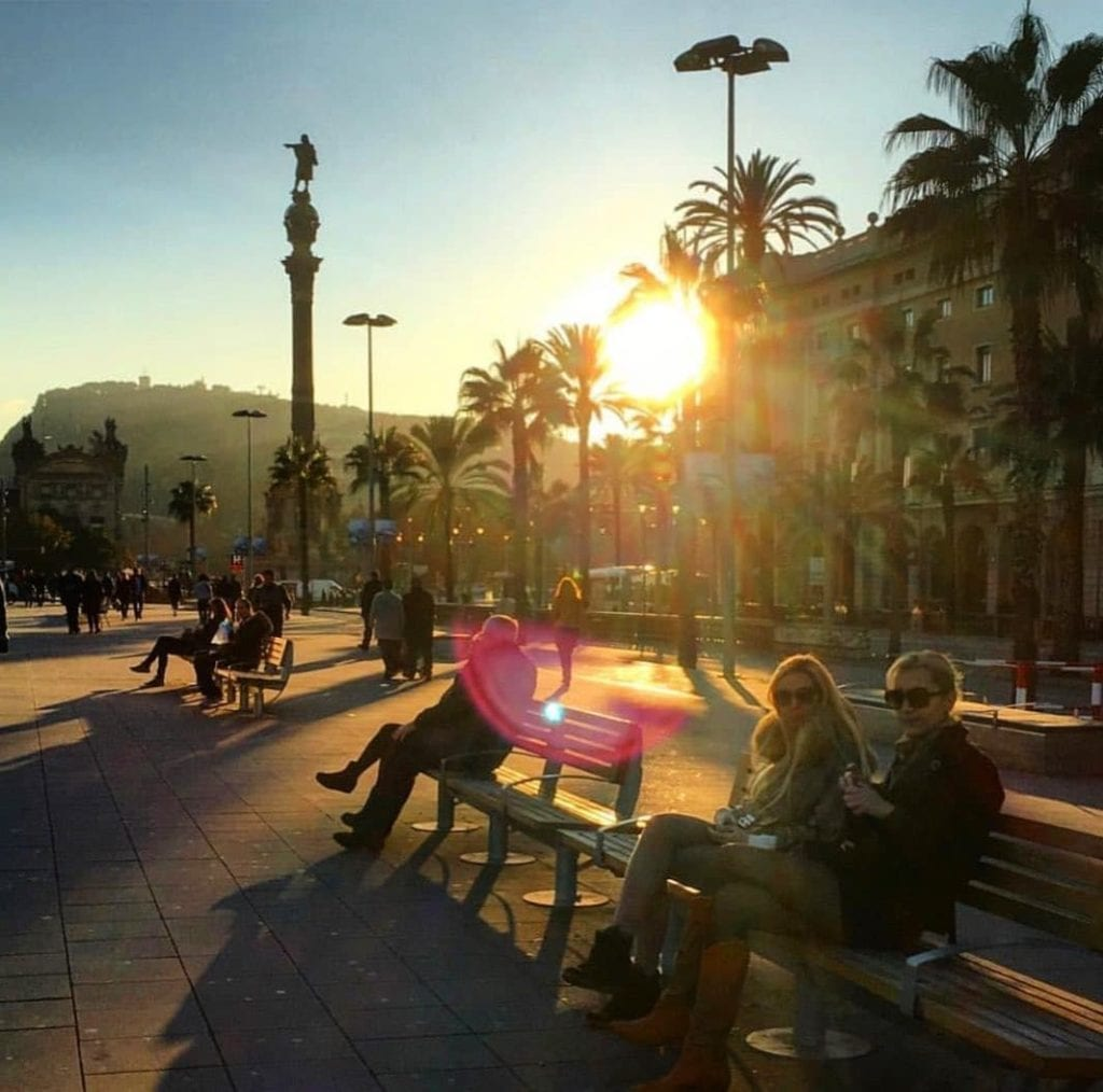 Many people sitting on benches during sunset along the Passeig de Colom, one of the most beautiful places in Barcelona.