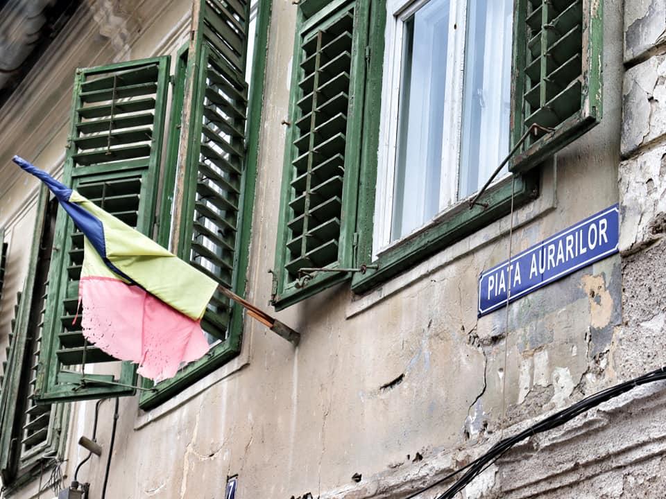 Romanian flag wind-blown around its pole in Piata Aurarilor in Sibiu, Romania