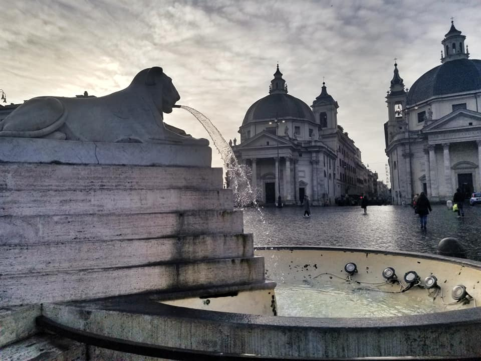 Piazza del Popolo with the lion fountain in the foreground, water coming out of its mouth.