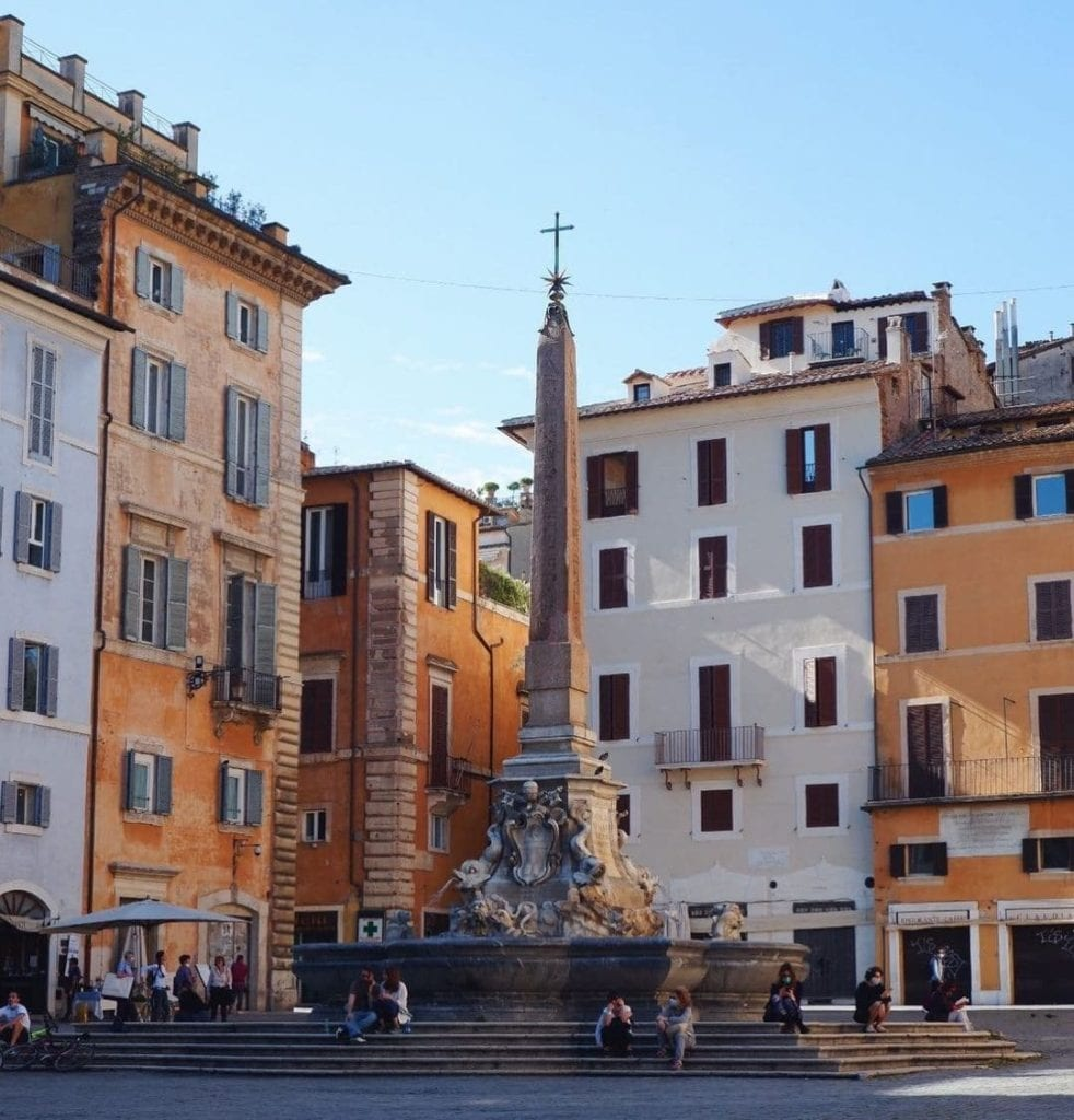 The obelisk in Piazza della Rotonda, with people sitting on its steps and the orange and white buildings in the background.