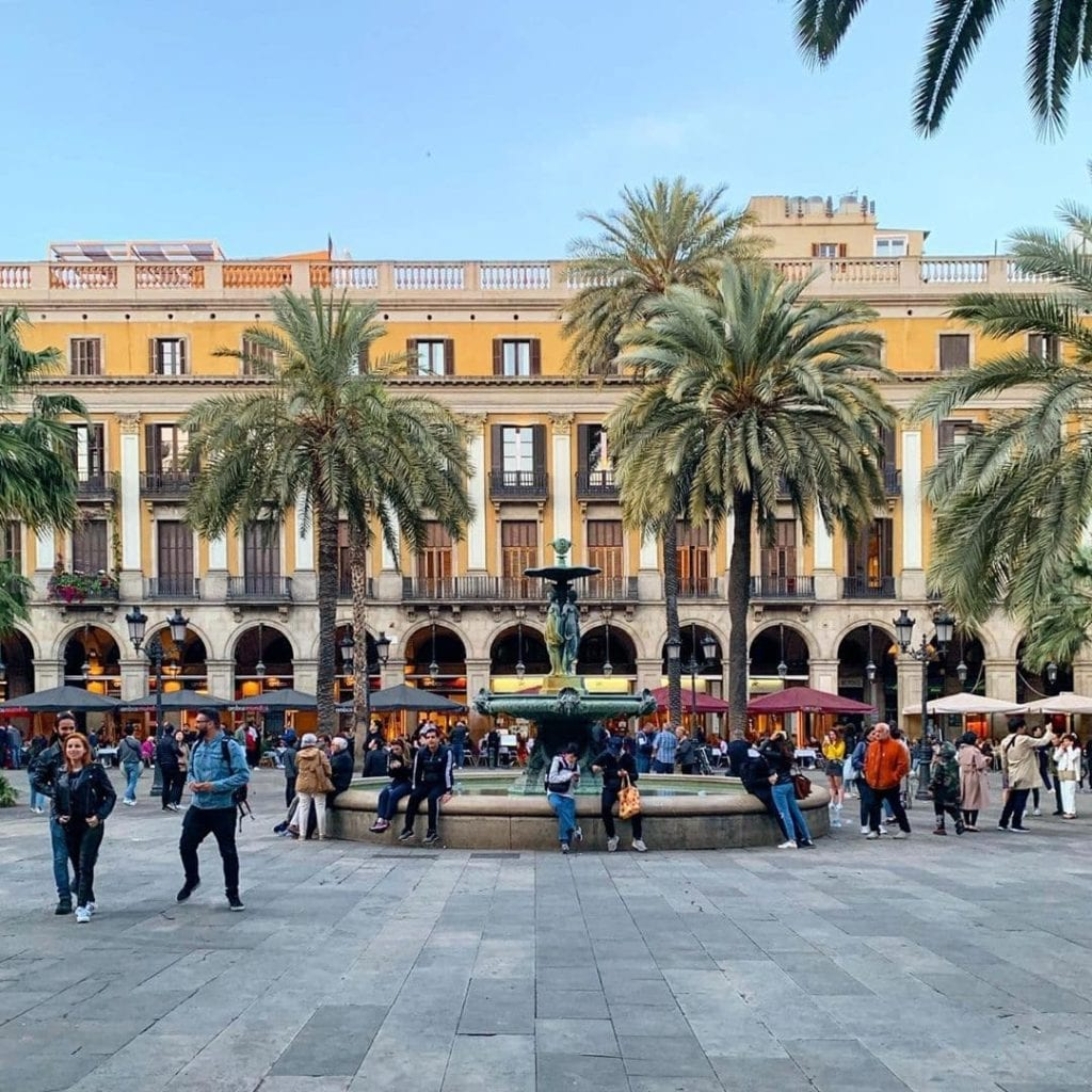 Many people mingling under palm trees in front of a fountain at Placa Reial in Barcelona.