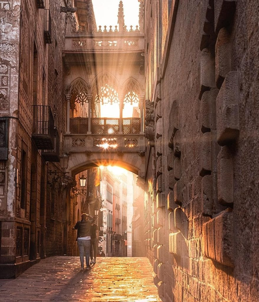 A few people walking under Pont del Bisbe at sunrise, one of the most beautiful places in Barcelona.