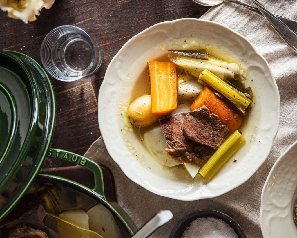 Bowl of pot-au-feu with glasses and ceramics surrounding it on a wooden table.  One of the most traditional French foods.
